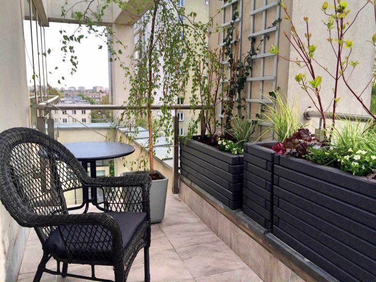 Ogród na balkonie. Doskonała metamorfoza balkonu w apartamentowcu. Na balkonie znalazły się rosliny i komplet wypoczynkowy.