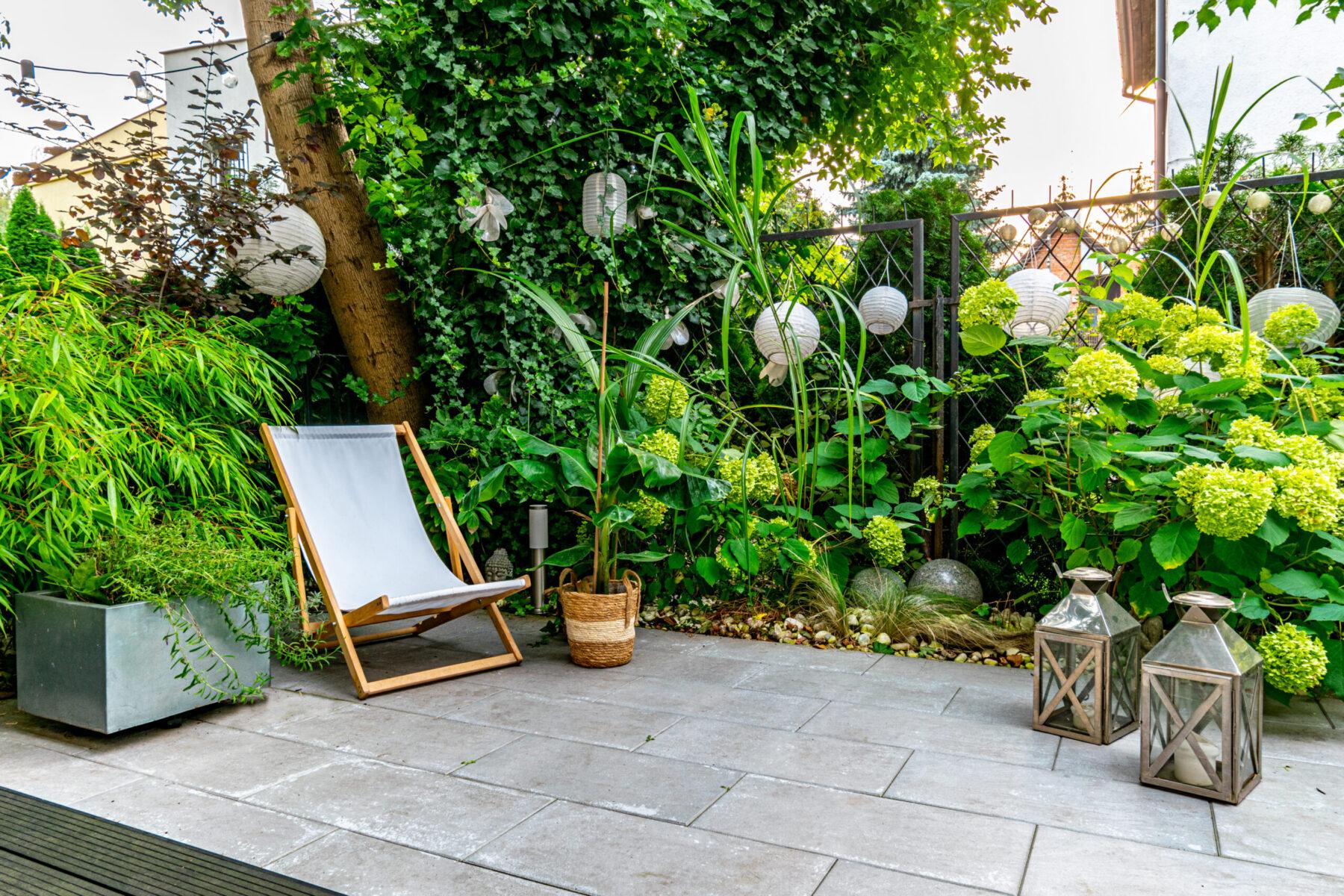 rośliny egzotyczne w ogrodzie, biały leżak i lampiony