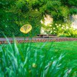 ogród z żółtym fotelem zanurzony w zieleni